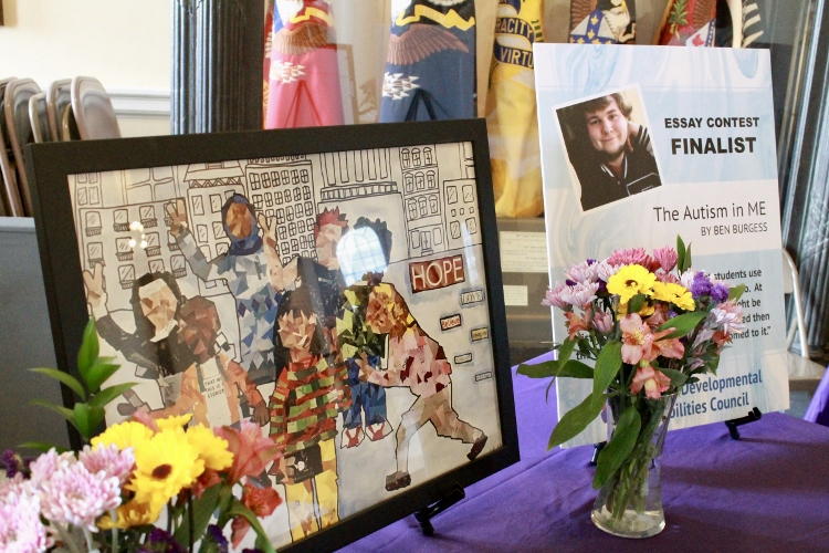 Display of artwork, a poster highlighting one of the essay winners, and vases of flowers at the Inclusion Ceremony
