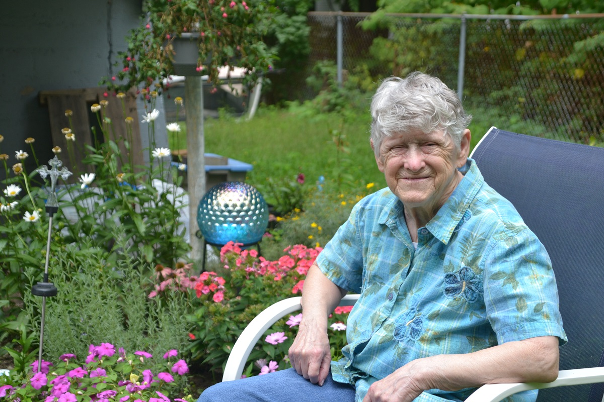 Vanessa Munsey sits in her garden. Behind her are pink and white flowers and a garden globe.